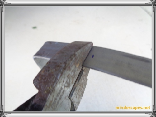 pliers gripping steel strip, making a second bend for the portion that hangs over the door