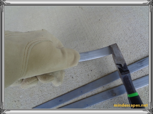 gloved hand showing using thumb to bend a curved hook from the metal strip