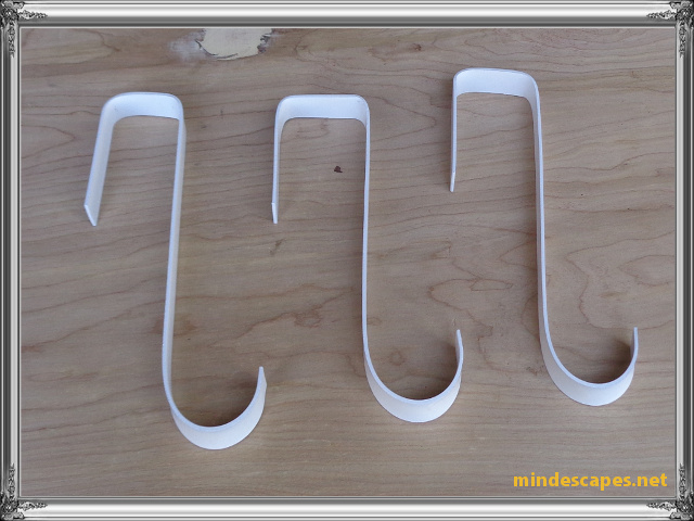 3 hooks painted white laying on wooden board